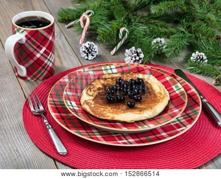 Close up view of a festive Christmas breakfast meal and coffee with evergreen branches on top of rustic wood.