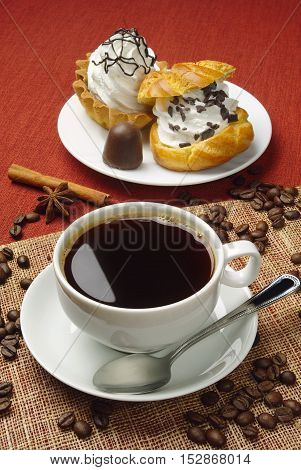 Cup of hot coffee and sweet cakes
