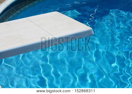 White diving board and crystal clear blue swimming pool