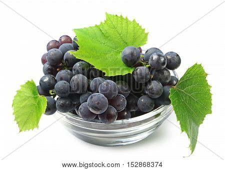 Ripe grapes with leaves in a glass cup on white