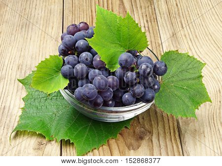 Ripe grapes with leaves in a glass cup on wooden background