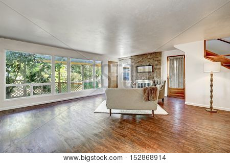 Spacious Living Room With Large Windows And Polished Hardwood Floor
