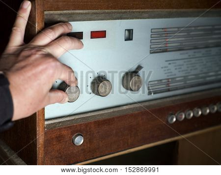 A male hand pushing a volume knob on a looking retro receiver shallow depth of field