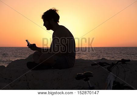 Silhouette Of Young Hipster Man Sitting With Smartphone On Background Of Sunset And Sea, Near His Bi