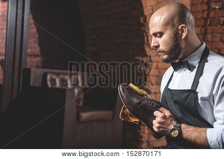 artificer polishing boots with a rag in front of a leather chair, selective focus