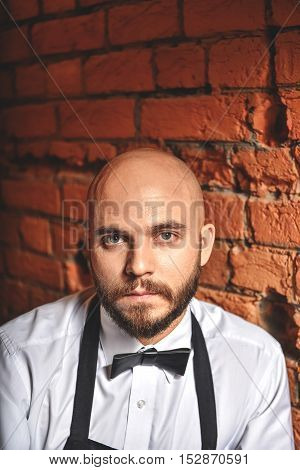 face of a bald calm worker in uniform standing against a brick background