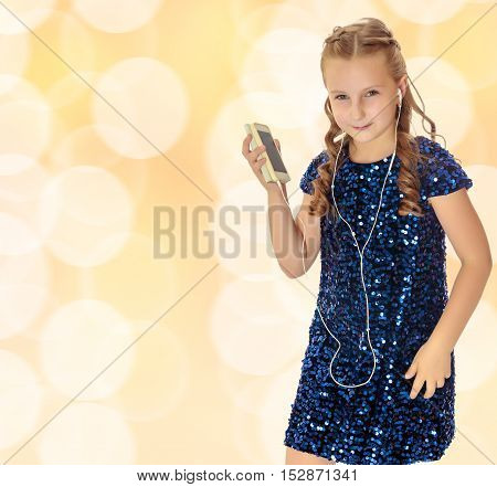 Elegant little girl in a festive, glittering, blue dress, holding a mobile phone . She listens to music through headphones. Christmas background with white snowflakes, circles.