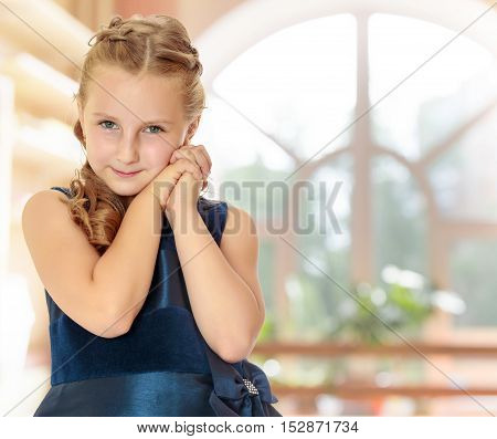 Cute little Caucasian girl in a dark blue dress, folded hands near the face . close-up. In a room with a large semi-circular window.