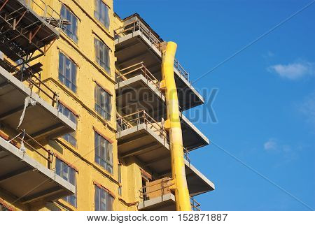 yellow building in construction with downfall slide on blue sky