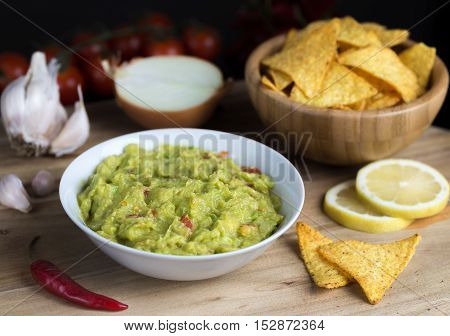 Guacamole in white bowl on natural wooden desk with tortilla chips.
