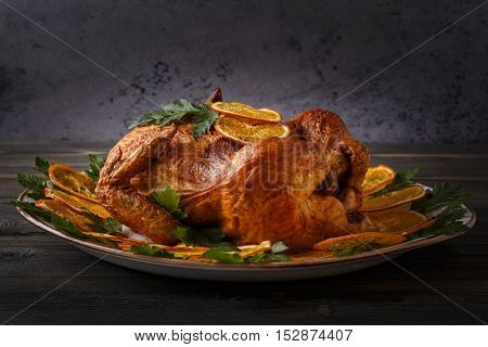 Homemade roasted whole chicken with parsley and oranges selective focus.