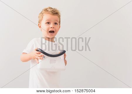 Mom, turn more. Studio shot of surprised little boy posing for camera while holding virtual reality device in his hands isolated on grey background