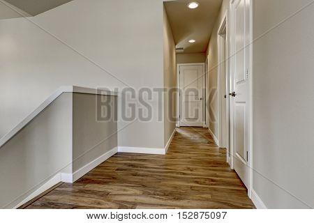 Empty Hallway With Hardwood Floor, Beige Walls And Staircase