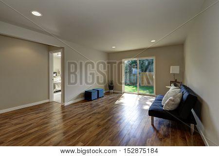 Empty Room Downstairs With Hardwood Floor And Glass Door