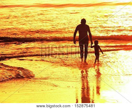 Father and little son silhouettes on sea sunset background