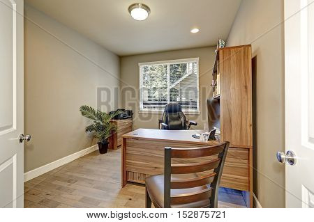 Home Office Interior With Wooden Furniture And Leather Armchair