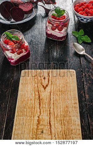 Healthy breakfast of beetroot and raspberry puree, mash of yogurt and oats and fresh berries