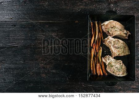 Porkchop and baby carrots baked on metal baking tray