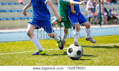 Boys play soccer match on sports field. Youth football league