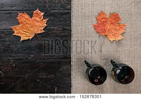 Still life with two empty tea cups and fallen maple leaf on the half covered table. Flat lay