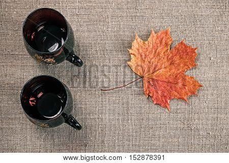 Still life with two empty tea cups and fallen maple leaf. Flat lay