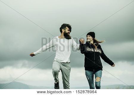 Couple Bouncing On Gray Sky