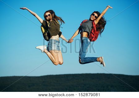 two pretty sexy cute girls or women in jeans and shorts with backpacks outdoor on sunny day jumping on blue sky background