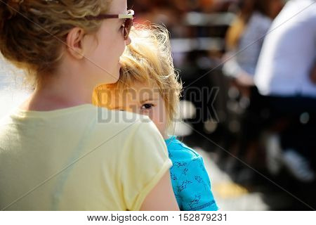 Mother young woman in sunglasses holds happy son baby boy with blonde hair in blue shirt sunny day outdoor in street on blurred background