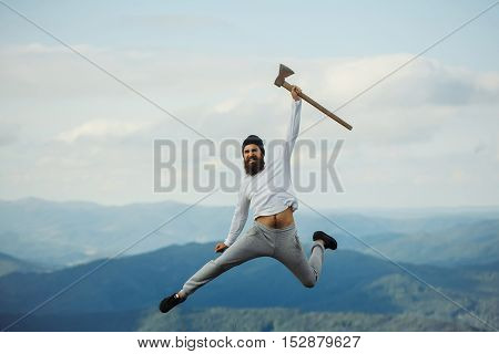 Handsome man bearded hipster with beard and moustache in hat jumps with axe on mountain top on cloudy sky