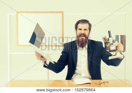 Angry man businessman male scientist hipster with laptop and microscope shouts furiously in office with board for copy space on white background