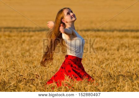 Girl in red skirt whirling in wheat field arms spread out