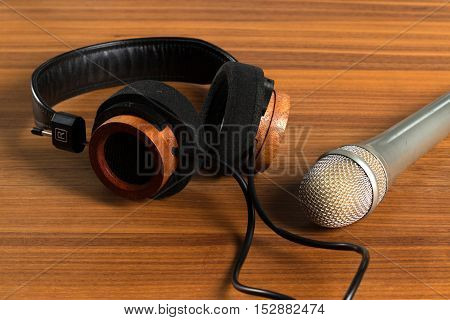 Elegant headphones and a studio microphone on a wooden table. Tools for vocals