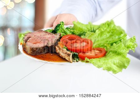 Waiter giving a Gorgeous Club steaks and vegetables on a plate