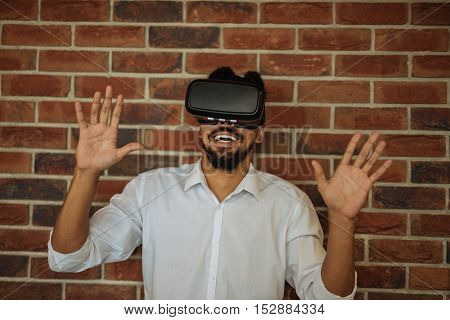 African american man trying VR glasses in an office.
