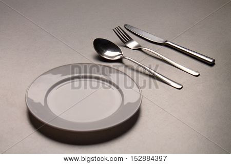 Empty plate with spoon knife and fork on a white background. low key picture