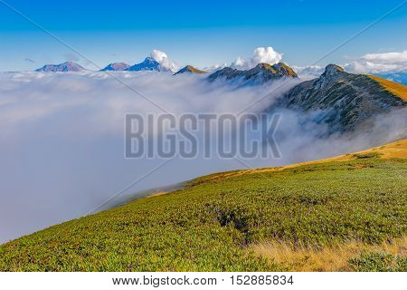 Clouds cover mountain tops at autumn evening time. Caucasus. Russia.