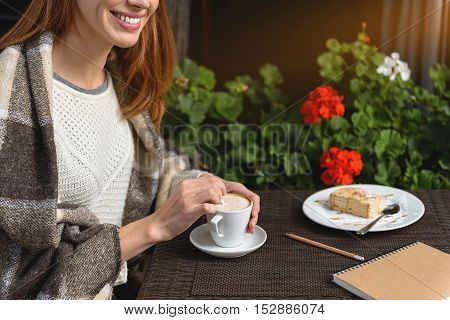 Happy young woman is relaxing in cafeteria outdoors. She is mixing coffee by spoon and smiling. Girl is warming up by blanket