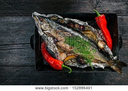 Whole salmon fish baked on tray in foil sheet with lemon, onions and spices. Flat lay