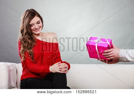 Couple and holiday concept. man holding present in hands surprising cheerful woman with gift box