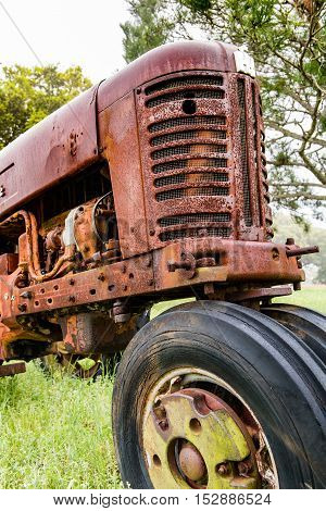 Front end view of an old abandoned rusty tractor