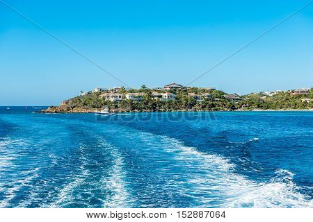 Peninsula of St. Thomas island out into the Caribbean sea with small boat. View off the back of the boat with boat wake.
