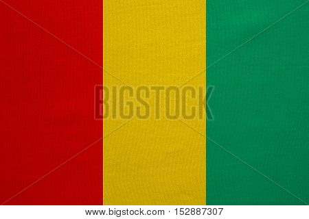 Guinean national official flag. African patriotic symbol banner element background. Correct colors. Flag of Guinea with real detailed fabric texture accurate size illustration