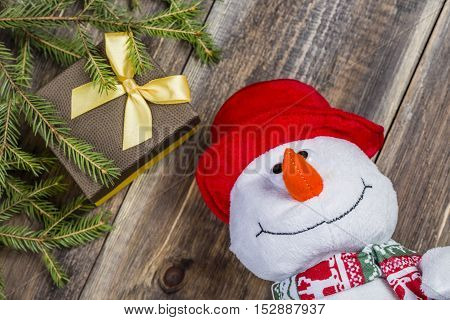 Funny snowman in red hat with gift box and spruce branch on nice wooden background. Selective focus
