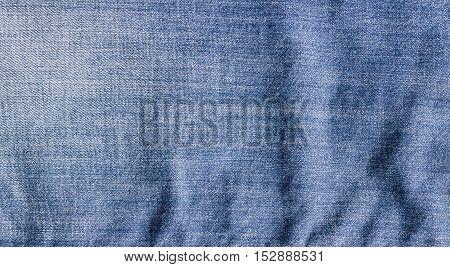 Blue crumpled denim jeans texture. Blue jeans background.