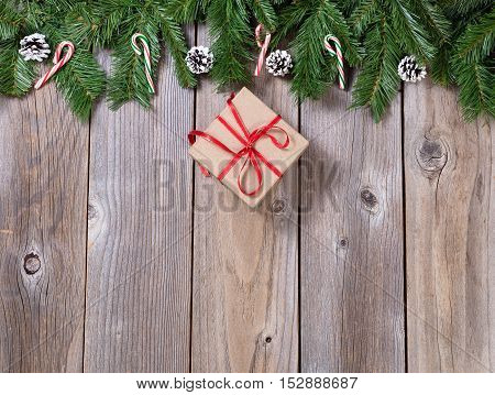 Christmas holiday wooden background with fir branches and gift box forming upper border