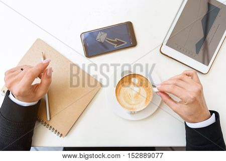 Top view close up of businesswoman hands holding cup of coffee. Notebook, tablet and smartphone sending message on table
