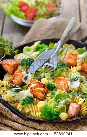Italian pasta with fried cuts of salmon fillet, horseradish and a sauce of cream and leek served in an iron frying pan with a side salad in the background