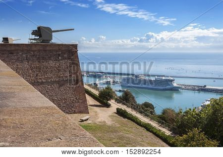 View of the Barcelona port and cruise ship with the ancient citadel with cannons on the mountain of Montjuic