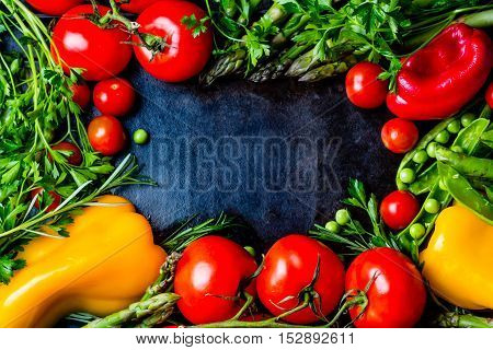 Food background - raw organic vegetables, fresh ingredients for healthily cooking on black background, top view. Vegetarian or healthy food concept. Background layout with free text space. frame