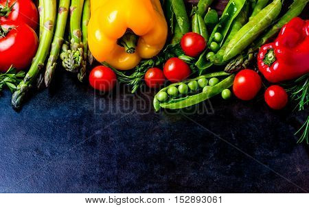 Food background - raw organic vegetables, fresh ingredients for healthily cooking on black background, top view. Vegetarian or healthy food concept. Background layout with free text space.